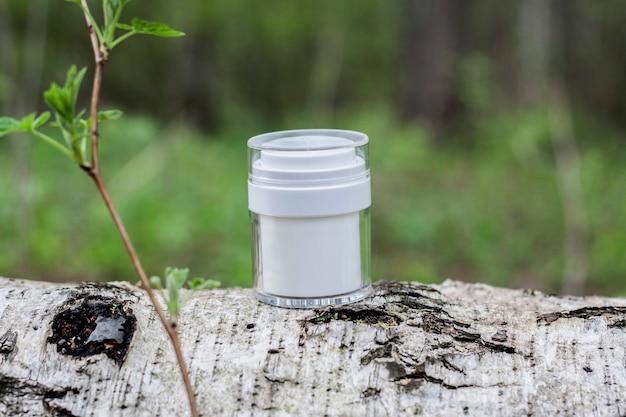 Um frasco branco de cosméticos em um tronco na floresta, um galho com folhas verdes