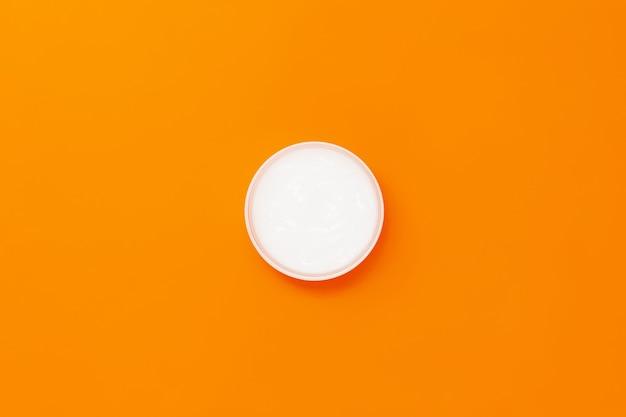 Um frasco com uma máscara hidratante de cabelo branco em uma laranja