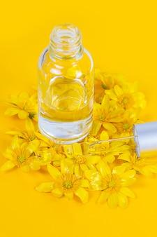 Um frasco com uma pipeta de soro em um fundo amarelo cercado por flores da primavera
