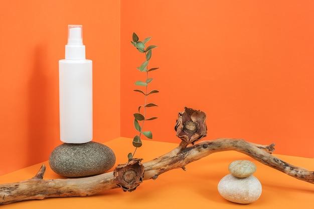 Um frasco cosmético branco em branco na rocha e o galho de eucalipto na sala laranja