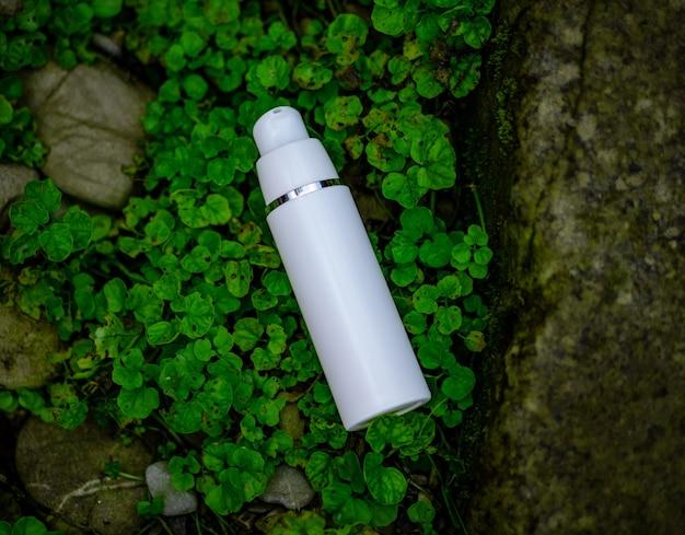 Um frasco de cosmético branco encontra-se na grama. composição natural