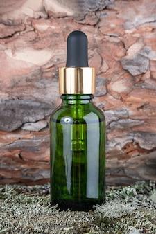 Um frasco de cosmético de vidro verde com soro, óleo essencial em musgo verde e casca de árvore