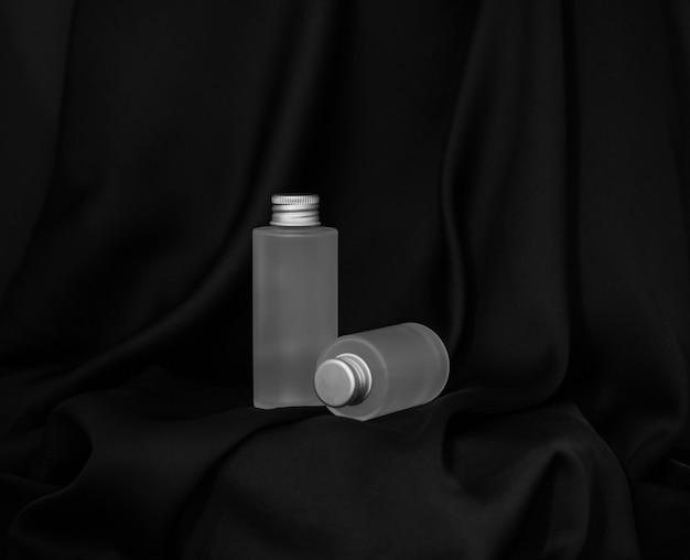 Um frasco de cosmético está de pé e o segundo está sobre um fundo de seda preta