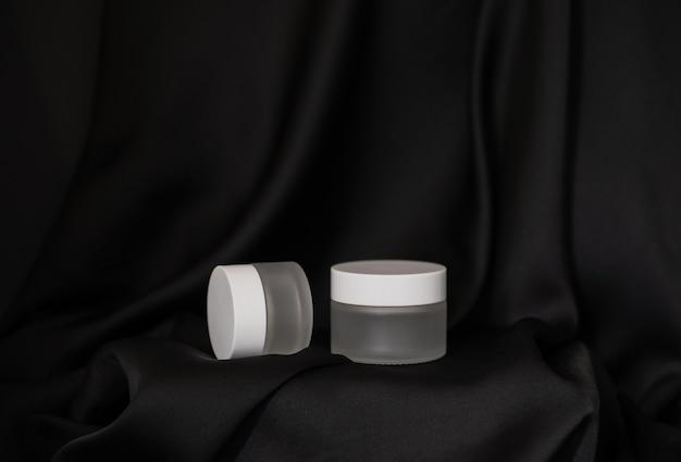 Um frasco de cosmético fica em um fundo de seda preta, o segundo frasco de cosmético fica de lado