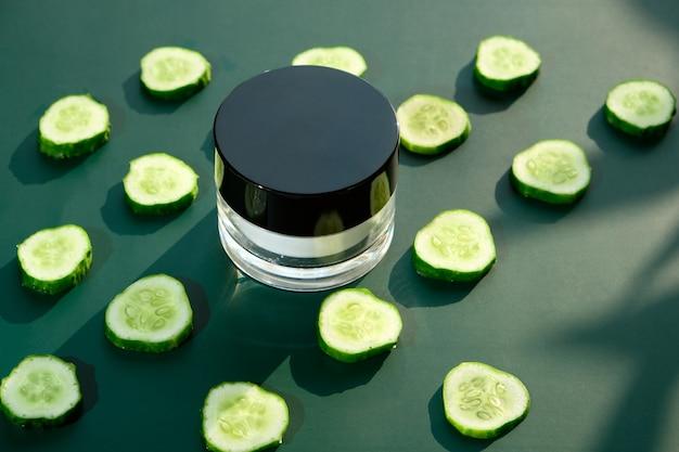 Um frasco de creme de pepino natural em uma parede verde escura. conceito de creme de pepino fresco com pepino fresco fatiado