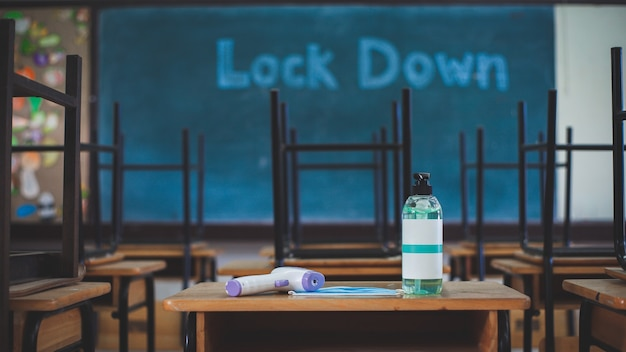Um frasco de desinfetante para as mãos, termômetro digital e máscara facial em cima de uma mesa na sala de aula de uma escola. a escola fechou devido ao surto de covid-19 e uma mensagem