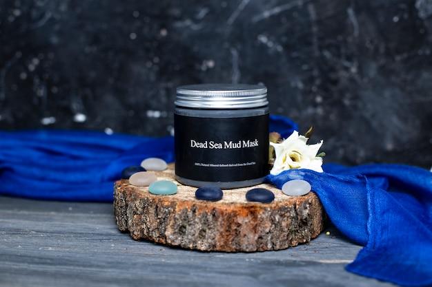 Um frasco de máscara de lama de mar morto de cuidados com a pele natural com tampa de prata em madeira