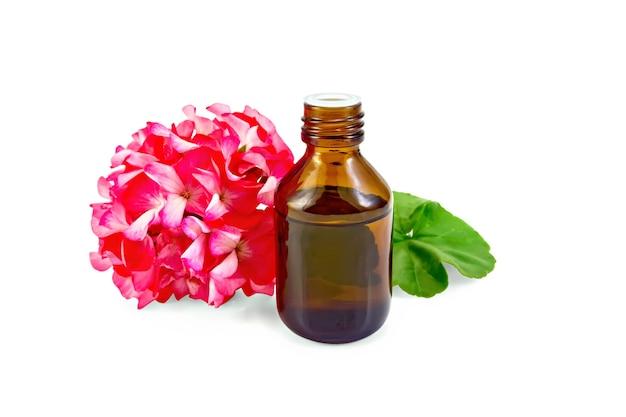 Um frasco de óleo escuro com folha verde e flor de gerânio rosa com um tom claro em fundo branco