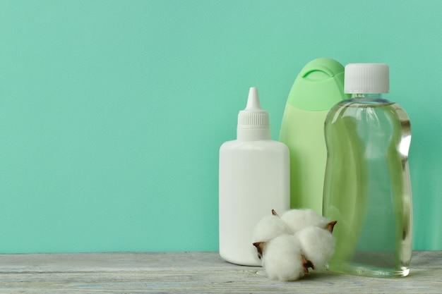 Um frasco de óleo, um frasco de xampu, talco para bebês na prateleira