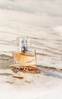 Um frasco de perfume à beira-mar é envolvido por uma onda. areia amarela na praia, cosméticos marinhos e fragrâncias.