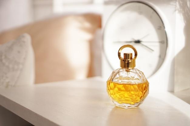 Um frasco de perfume amarelo na mesa de cabeceira