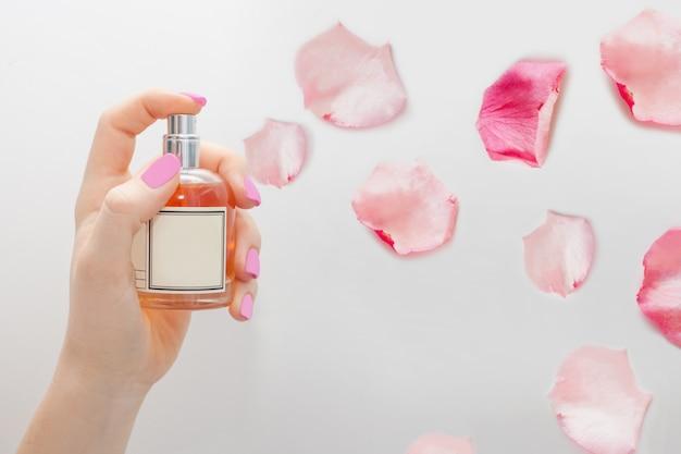 Um frasco de perfume, do qual pétalas de rosa voam quando o dedo pressiona o spray. o conceito de perfumes, compostos e ingredientes aromáticos, aromas delicados.