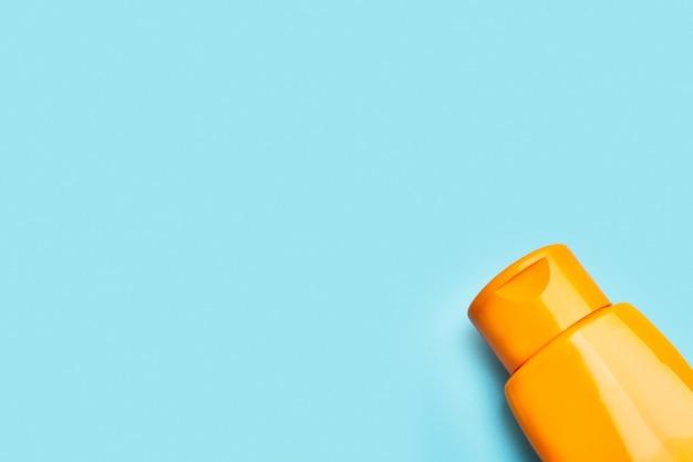 Um frasco de protetor solar laranja de plástico em um fundo azul claro com espaço de cópia