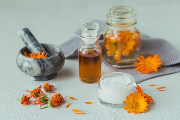 Um frasco de tintura ou infusão de calêndula, pomada, creme ou bálsamo com flores de calêndula frescas e secas na luz