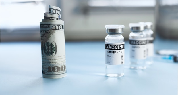 Um frasco de vacina contra o coronavírus e uma nota de cem dólares