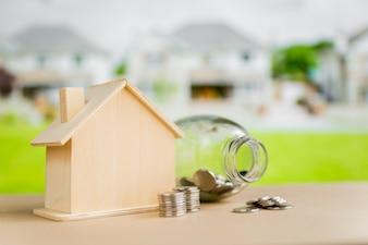 Um frasco de vidro aberto; moedas perto do modelo de casa de madeira na mesa ao ar livre