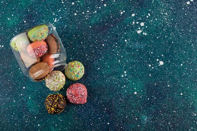 Um frasco de vidro cheio de pequenos donuts coloridos.