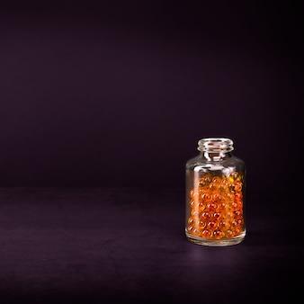 Um frasco de vidro com comprimidos de cor amarelo laranja brilhante em uma parede lilás.