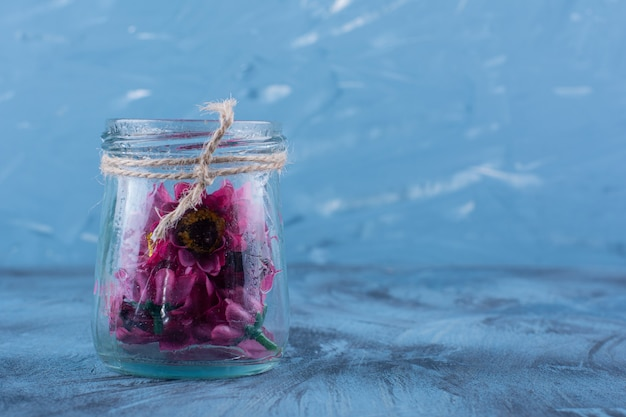 Um frasco de vidro com flores artificiais roxas em azul.