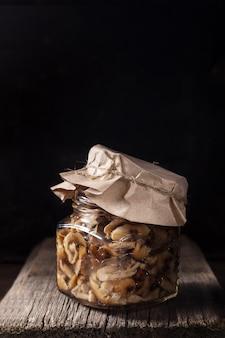 Um frasco de vidro com floresta em conserva cresce rapidamente agarics de mel sob a tampa de papel na prancha de madeira velha.