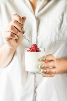 Um frasco de vidro com iogurte caseiro com framboesas nas mãos de uma mulher