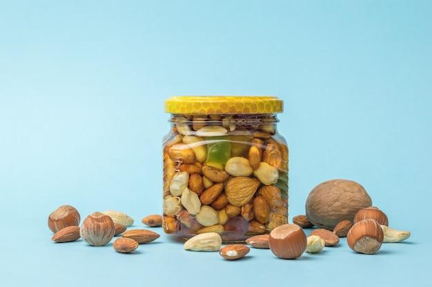 Um frasco de vidro com mel, nozes e nozes espalhadas sobre um fundo azul. um remédio nutritivo natural.