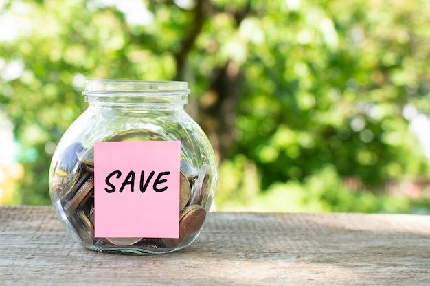 Um frasco de vidro com moedas e a inscrição save em uma mesa de madeira. orçamento para investimento. conceito financeiro.