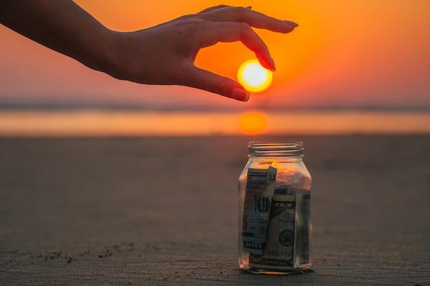 Um frasco de vidro com moedas e notas na praia contra o pôr do sol. o conceito de acúmulo de dinheiro para viagens.