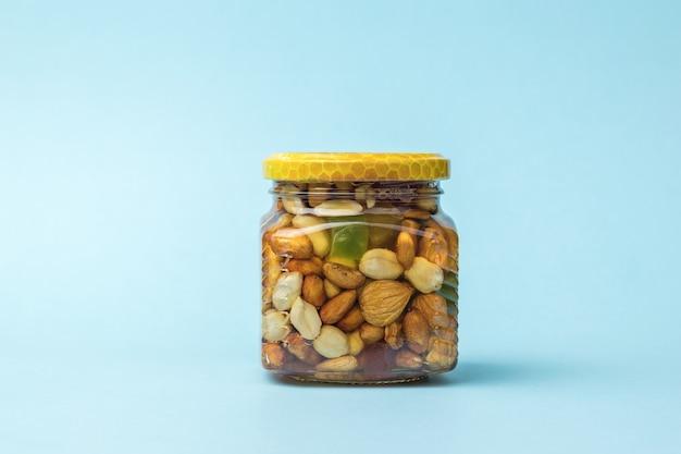 Um frasco de vidro com nozes e mel em um fundo azul claro. um remédio nutritivo natural.