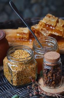 Um frasco de vidro com pólen, mel e própolis em uma placa de madeira fica em uma mesa de vime