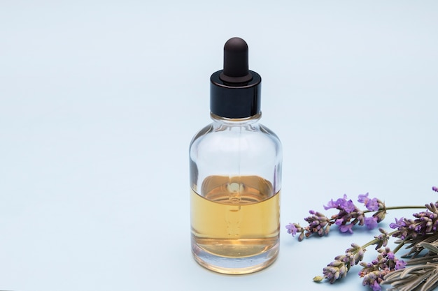 Um frasco de vidro com um conta-gotas cheio de um líquido sobre um fundo azul com flores de lavanda.