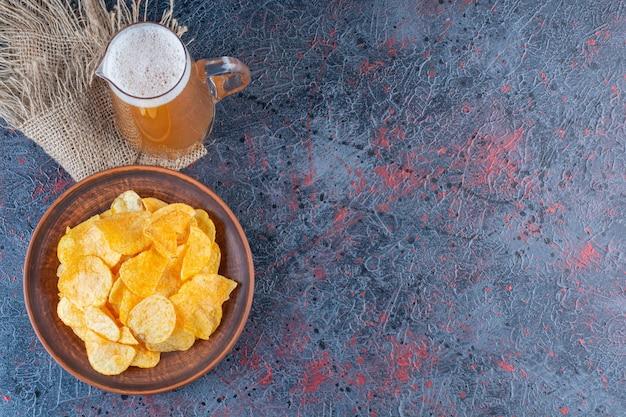 Um frasco de vidro de cerveja dourada gelada com batata frita em um fundo escuro.
