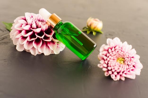 Um frasco de vidro verde com óleo cosmético ou essencial para cuidados com o rosto e o corpo em um fundo preto com uma flor de dália roxa.