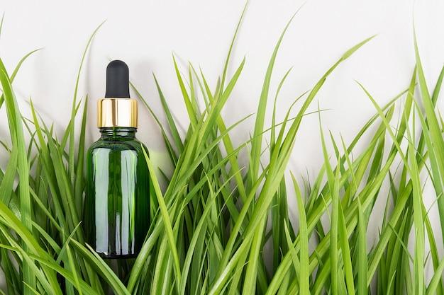 Um frasco de vidro verde com soro, óleo essencial, colágeno ou outro produto cosmético entre a grama verde sobre fundo branco. conceito cosmético natural organic spa maquete vista superior.