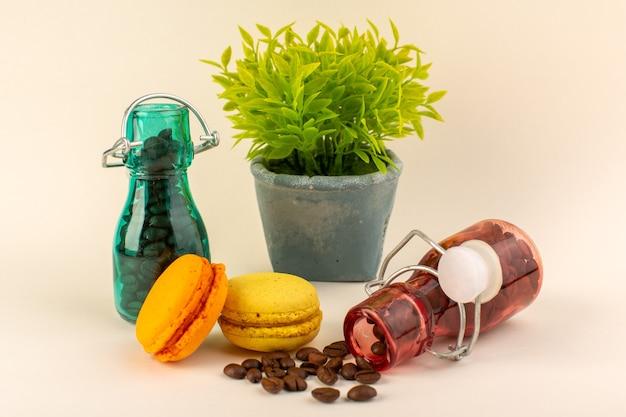 Um frasco de vista frontal com macarons franceses de café e planta verde na superfície rosa