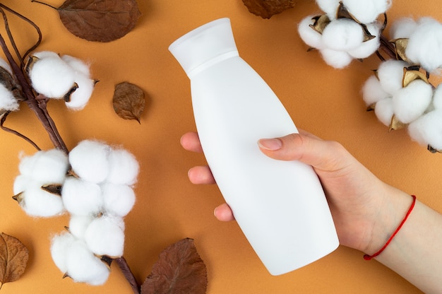 Um frasco de xampu em um fundo laranja. layout para sua etiqueta. cosméticos naturais.