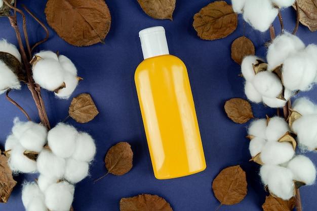 Um frasco de xampu sobre um fundo azul. layout para sua etiqueta. cosméticos naturais.