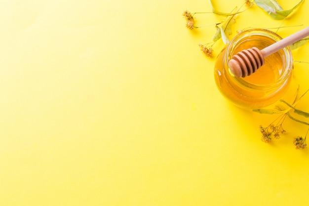 Um frasco do mel líquido das flores do linden e uma vara com mel na superfície amarela. espaço da cópia