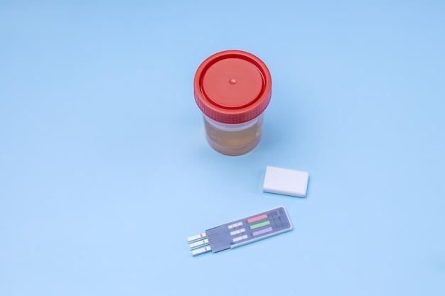 Um frasco para testes de urina e tiras de teste