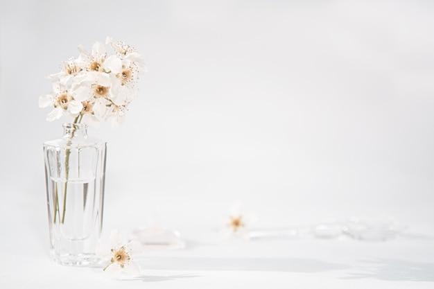 Um frasco transparente de perfume e um raminho com flores brancas ao lado do qual se encontra uma vareta de vidro e uma tampa