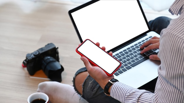 Um freelancer masculino sentado no chão e usando um telefone inteligente enquanto trabalhava com o laptop no escritório em casa.