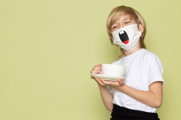 Um frotn vista garoto loiro adorável doce bonito em camiseta branca e máscara engraçada segurando a xícara de café na mesa de pedra colorida