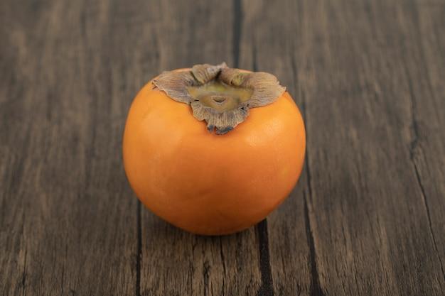 Um fruto de caqui maduro colocado em uma superfície de madeira