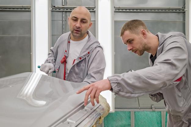 Um funcionário da oficina de pintura de carrocerias elimina um pequeno defeito de metal com uma ferramenta manual especial