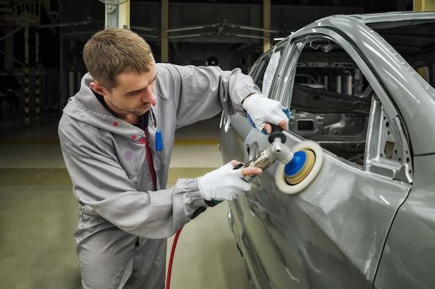 Um funcionário da oficina de pintura de carrocerias lustra a superfície pintada com uma polidora pneumática