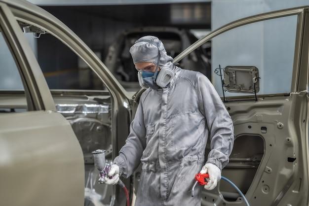 Um funcionário da oficina de pintura prepara a carroceria do carro para a pintura