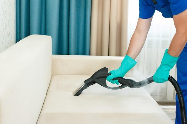 Um funcionário de uma empresa de limpeza fornece um serviço de limpeza química e a vapor para o sofá. limpador a vapor