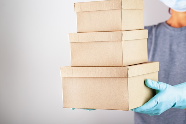 Um funcionário do serviço de entrega segura uma caixa com luvas e uma máscara para protegê-lo de vírus e doenças em um fundo branco.