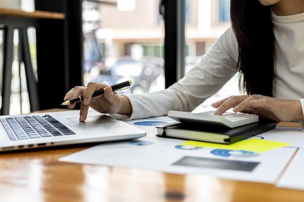 Um funcionário financeiro pressiona uma calculadora para verificar a exatidão dos dados financeiros da empresa em um laptop e prepara um resumo financeiro da empresa para levar para uma reunião com a gerência.
