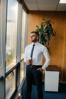 Um funcionário no escritório está parado perto da janela. finança.